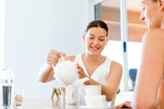 Young woman with her friend having tea at home Stock Image