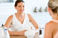Young woman with her friend having tea at home. Young women sitting at the kitchen table having tea with her friend Stock Photo