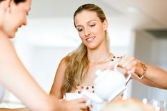Young woman with her friend having tea at home Royalty Free Stock Photos