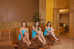 Young women sitting on loungers in front of sauna Stock Photos
