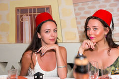Young women sitting in Moroccan restaurant and wearing fezes Stock Images