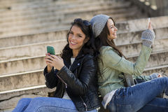 Young women sitting on the stairs with mobile phones Royalty Free Stock Images