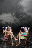 Young Women Sitting In Sunloungers In Rain Royalty Free Stock Photography
