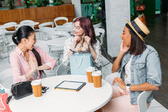 Young women sitting at table with paper cups and showing new stylish shoes, young girls shopping concept. Smiling young women sitting at table with paper cups stock photo