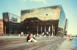 Young women sitting at waterfront near the Black Diamond, modern part of Royal Danish Library royalty free stock images