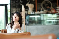 Young women sitting at wooden table in morning and using mobile. Young asia woman sitting at wooden table in morning and using mobile phone. she thinking and Royalty Free Stock Photos