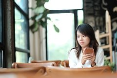 Young women sitting at wooden table in morning and using mobile. Young asia woman sitting at wooden table in morning and using mobile phone. she thinking and Royalty Free Stock Images