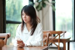 Young women sitting at workplace in morning and using mobile pho. Young asia woman sitting at workplace in morning and using mobile phone for checking something Stock Image
