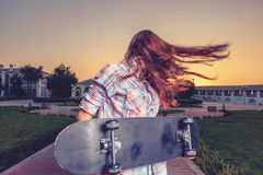 Young women with skatebord shaking her red hair Royalty Free Stock Images
