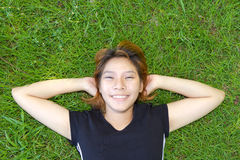 Young women sleep on grassland with her face smile Royalty Free Stock Photography