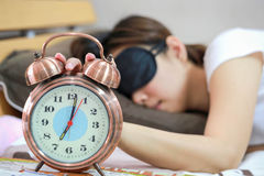 Young women sleepy in bed with blindfold and closed clock. Royalty Free Stock Images