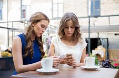Young women with smartphones and coffee at cafe Royalty Free Stock Image