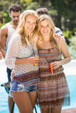 Young women smiling and having juice together Royalty Free Stock Image