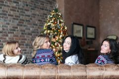 Young women smiling and looking at camera while sitting near Christmas tree Royalty Free Stock Photos