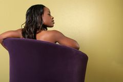 Young women in sofa. Young attractive afro-American women in sofa looking to her right, lot's of copy-space Royalty Free Stock Photo