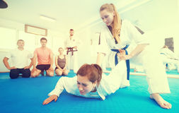 Young women in sparring work out painful techniques Royalty Free Stock Image