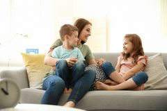 Young woman spending time with her children. Young women spending time with her children at home. Happy family stock image