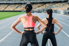 Young women in sportswear exercising on running track stadium stock photo