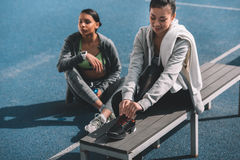 Young women in sportswear resting together on stadium Royalty Free Stock Images