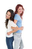 Young women standing back to back with interlocked hands Stock Images