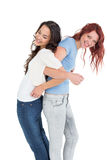 Young women standing back to back with interlocked hands Royalty Free Stock Photography