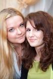 Young women standing cheek to cheek Royalty Free Stock Photos