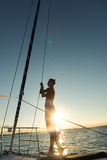 Young women standing on the edge of the sailboat Stock Photos