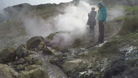 Young women standing on thermal field in clouds of steam hot springs stock video footage