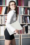 Young women stands near bookshelf Royalty Free Stock Images