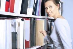 Young women stands near bookshelf Stock Photos