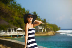 Young women in straw hat and stylish beach enjoying the tropical sun. Summer skin care concept. Pretty girl on vacation. Young woman in straw hat enjoying the Stock Image