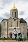 Young woman with a stroller at the front of the Cathedral of Saint Demetrius in Vladimir town royalty free stock photos