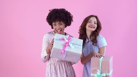 Young women studio isolated on pink women`s day holding gift boxes stock video