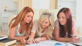 Young women studying while lying on the floor Royalty Free Stock Images