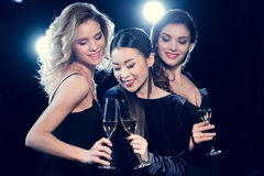 Young women in stylish dresses partying and drinking champagne together. Beautiful young women in stylish dresses partying and drinking champagne together Stock Photography