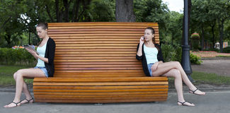 Young women on a summer park bench Royalty Free Stock Image