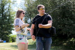 Young man and a woman with fishing rod on a river in Germany Royalty Free Stock Photos