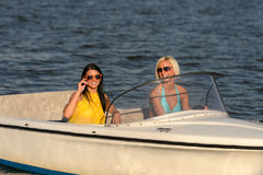 Young women in sunglasses sitting in motorboat Stock Photography