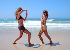 Young women on sunny beach. Two young women taking photos of each other on a sunny beach Stock Photos