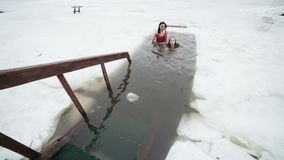 Young women swim in the ice hole. Young women in bathing suits swim in the ice hole in winter stock footage
