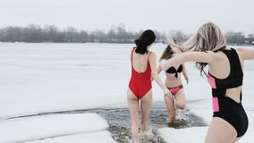 Young women in the ice hole. Young women in swimsuits frolic in the ice hole stock video