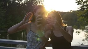 Young women take selfie at sunset. Young female friends taking selfie on smartphone in the park standing on a bridge at sunset with beautiful glare on the water stock video