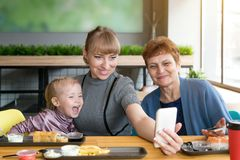 Grandmother`s daughter and granddaughter are photographed on the phone in a cafe. stock photos