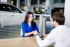 Salesman handing over car key to a customer woman. Young women taking a car for test drive and salesman providing her with keys stock photo