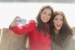 Young women taking photo with mobile phone Royalty Free Stock Image
