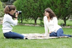 Young women taking pictures on natural background Royalty Free Stock Photos