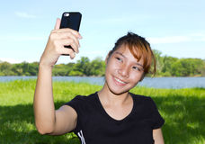 Young women taking pictures of themselves with a cellphone Royalty Free Stock Photo