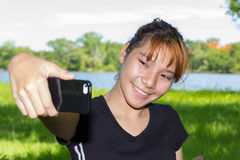 Young women taking pictures of themselves with a cellphone Royalty Free Stock Photography