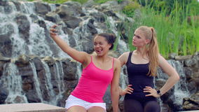 Young women taking selfie near waterfall. Multiracial women taking seflie. With phone in park. Joyful women in sport clothes taking self photo. Cheerful girls stock video