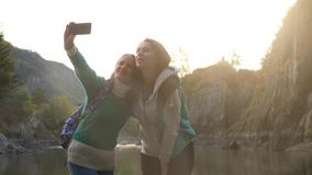 Young women is taking selfie on the phone against the background of big mountains and the green mountain river during. Beautiful women is taking selfie on the stock video